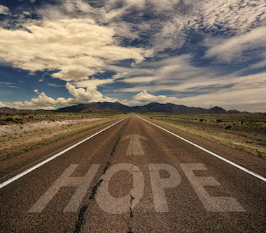 Conceptual image of desert road with the word hope and arrow