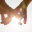 Couple holding hands towards the sun with bright sun flare between the silhouetted fingers on a pale blue sky close up view in a conceptual image.