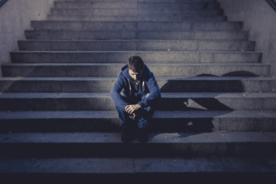 Young desperate man in casual clothes abandoned lost in depression sitting on ground street concrete stairs alone suffering emotional pain sadness looking sick in grunge lighting