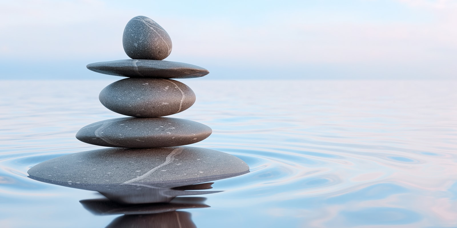 stack of stones sitting peacefully on water