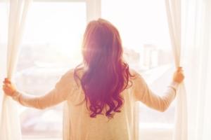 woman opens window to bright doors